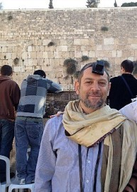 Amichai Lau-Lavie at the Western Wall wearing his tallit like a scarf, in solidarity with Women of the Wall.