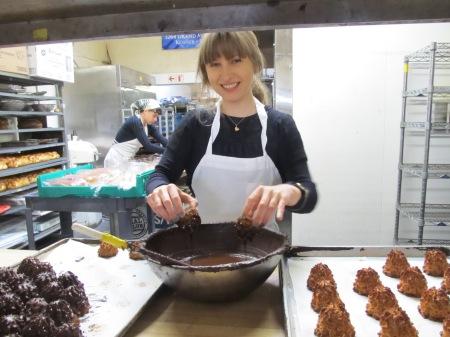 Katia Sukhotskaya of Grand Bakery dips coconut macaroons into chocolate. photo/bob jaffe