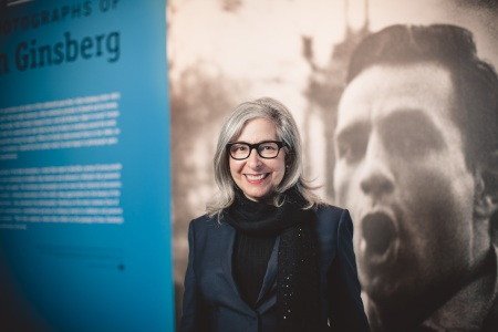 "Lori Starr stands in front of a wall display for the current exhibit ""Beat Memories: The Photographs of Allen Ginsberg."" photo/gary sexton"