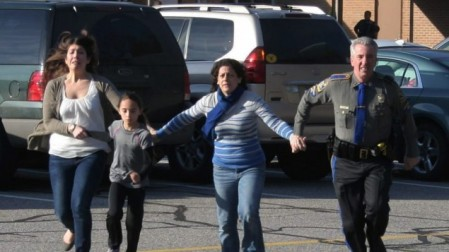 A police officer leads two women and a child from Sandy Hook Elementary School in Newtown, Connecticut, where a gunman opened fire, killing 26 people, including 20 children, December 14, 2012. (photo credit: AP/Newtown Bee/Shannon Hicks)
