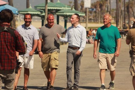 Rabbi Eliyahu Fink (second from right) strolls on the Venice Beach boardwalk with Church Hoppers (from left) Anthony 'Gladamere' Lockart, Kevin 'Rev Kev' Annas, and Jerry 'Doc' Bentley. (photo credit: Courtesy of T Group Productions)