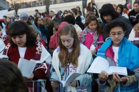 Eliza Moss-Horwitz, Lucy Sattler and Alexandra Schwartz pray with Women of the Wall. Schwartz (right) holds an empty Torah cover beneath her prayer book, symbolizing the Torah scroll the group was prevented from bringing in to the Kotel plaza. (photo credit: Courtesy of Moving Traditions)