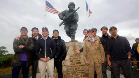 """Damian Lewis (second from left), Ben Caplan (fourth from left) and other """"Band of Brother"""" actors posed with WWII veteran JIm 'Pee Wee' Martin at Major Dick Winters statue in Normandy. (Courtesy)"""