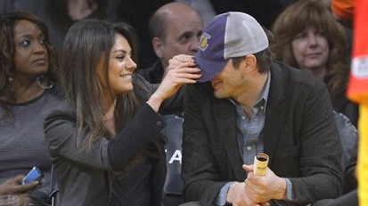 'They' are not pregnant. Actress Mila Kunis playfully pulls down the hat of actor Ashton Kutcher before a Los Angeles Lakers' NBA basketball game against the Utah Jazz, January 3, 2014, in Los Angeles. (photo credit: AP/Mark J. Terrill)
